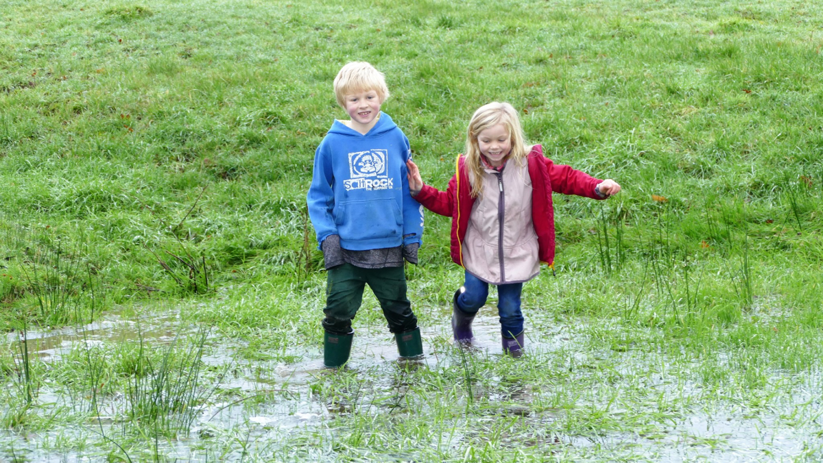 Kids in big field puddle