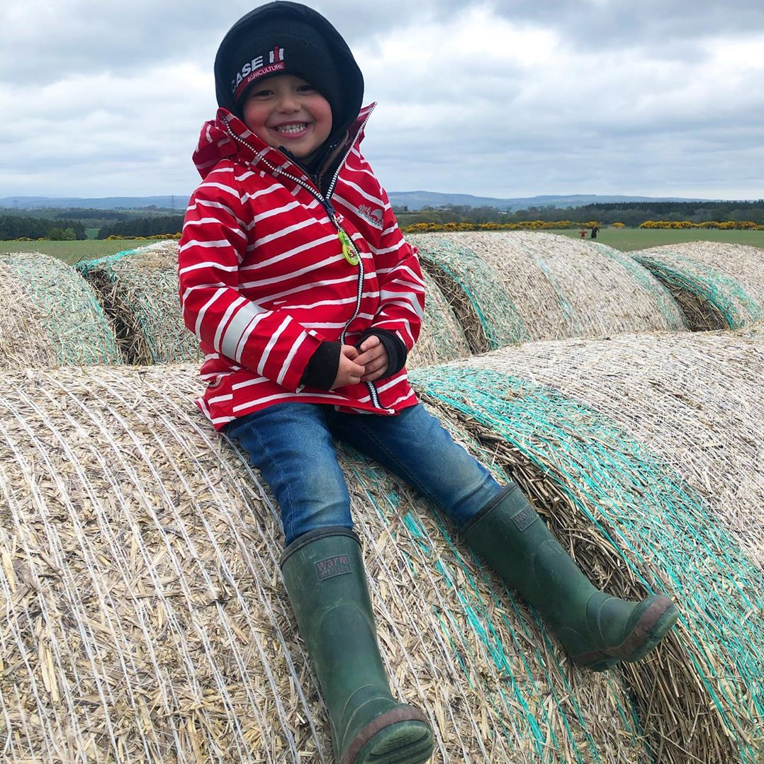 kid on a hay bale